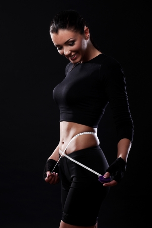 losing weight: Happy fitness girl measuring her waistline over black background Stock Photo