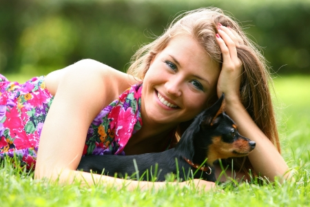 Happy woman lying  on the grass with her dog in the park photo
