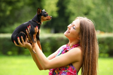 Happy young woman with her dog in the park photo
