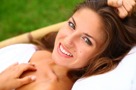 Young and happy woman relaxing on the deckchair photo