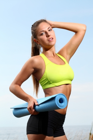 Sexy fitness woman holding mat for fitness on the beach photo