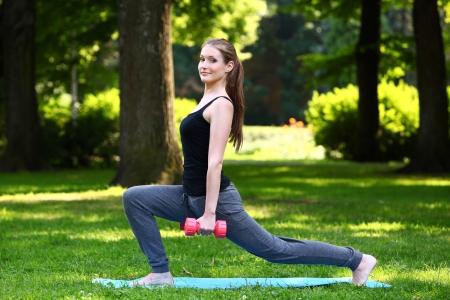 lunges: Mujer joven haciendo estocadas con mancuernas en el parque