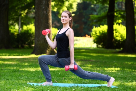 lunges: Young woman doing lunges with dumbbells in the park