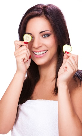 Happy girl in towel holding cucumber slices photo