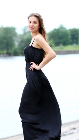 Beautiful woman in black dress by the river photo