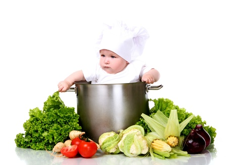 Cute baby chef with big pot and vegetables over white background Stock Photo - 15646422