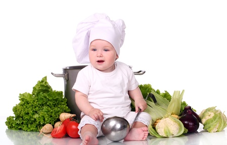 Cute baby chef with big pot and vegetables over white background photo