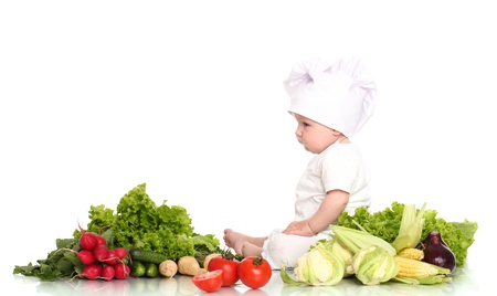 Cute baby chef with different vegetables over white background photo