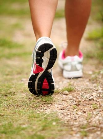 caminando: Primer plano de las piernas femeninas correr en una pista