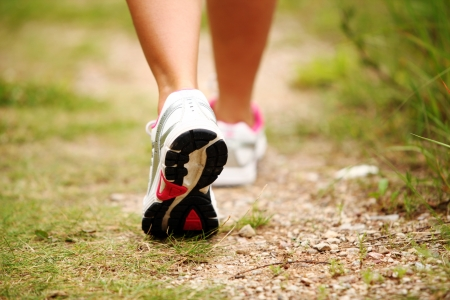 person walking: Closeup of female legs jogging on a trail