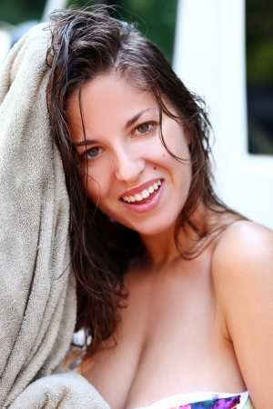 Young and beautiful woman is drying her wet hair photo