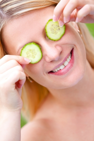 Young and happy woman with cucumber slices over her face photo