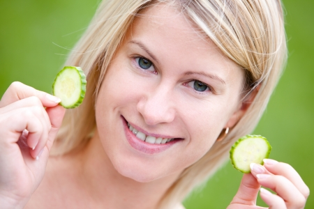 Portrait of happy woman with cucumber slices  photo