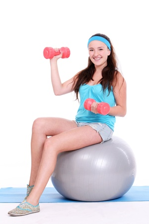 Woman working out with dumbbells on fitness ball over white background photo