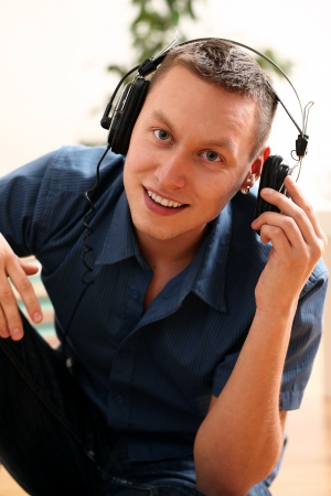 Young guy with headphones enjoying music at home Stock Photo
