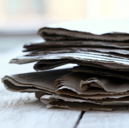 Stack of old newspapers on wooden table  photo