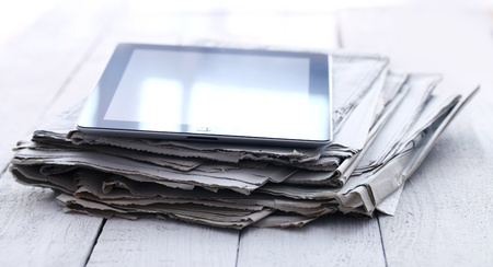 Stack of old newspapers and a tablet pc on the wooden table photo