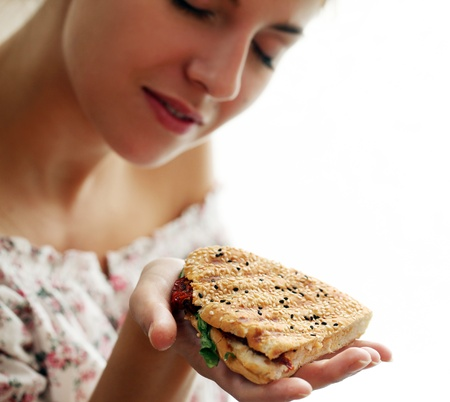 comiendo pan: Mujer que sostiene s�ndwich fresco en la mano