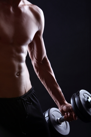 Strong and muscular guy with dumbbell over black background  Stock Photo