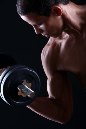 dumbell: Strong and muscular guy with dumbbell over black background  Stock Photo