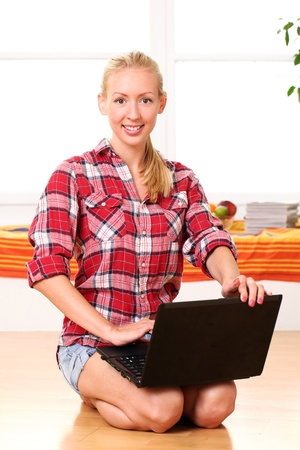 Young and happy woman with laptop on the floor photo