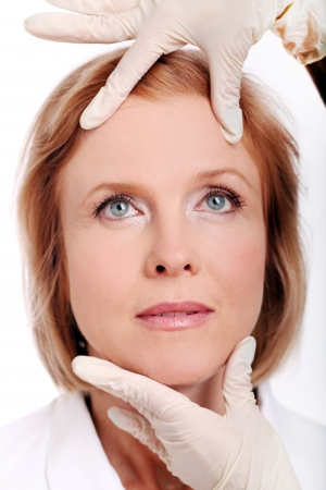 Face of woman and doctor hands in gloves. Plastic surengy concept. photo