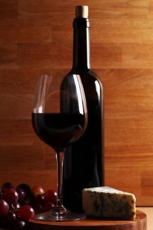 tabla de quesos: Vino rojo y queso azul sobre la superficie de madera