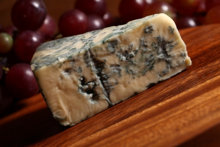 Slice of blue cheese and grape on the wooden surface photo