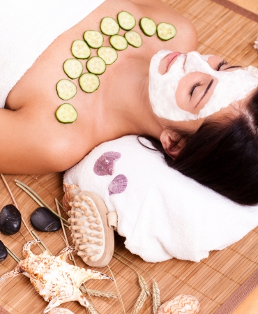 Young and happy woman relaxing with facial mask  photo