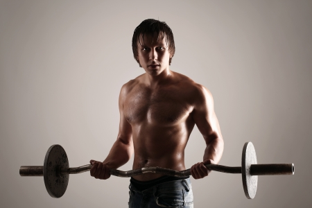 Young and muscular guy holding a barbell photo