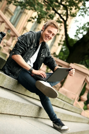 Young and happy student with laptop sitting on a stairs photo