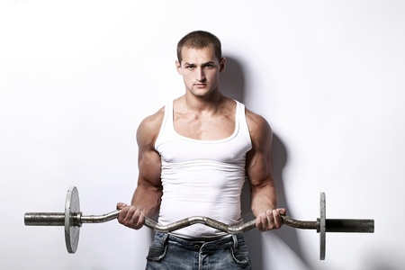 sportsman: Young and muscular man working out with barbell