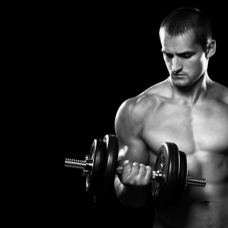 workout gym: Handsome muscular man working out with dumbbells over black background