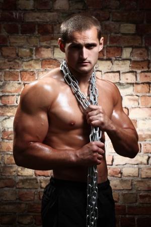 desnudo masculino: Hombre muscular con cadenas en sus hombros contra una pared de ladrillo