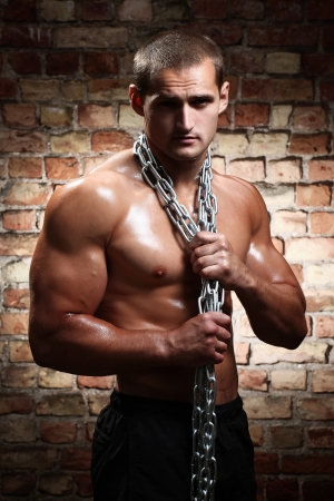 nude male: Muscular man with chains on his shoulders against a brick wall