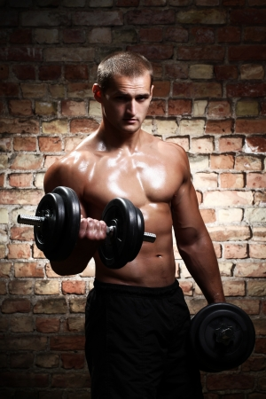 Young and muscular guy with dumbbells over brick wall photo