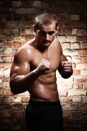 Young and muscular fighter against a brick wall photo
