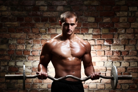 Young guy with muscular body with barbell over brick wall photo