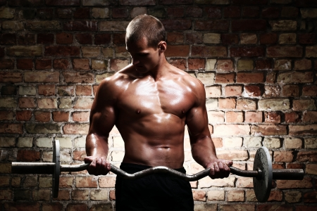 levantando pesas: Chico joven con cuerpo muscular con pesas sobre la pared de ladrillo