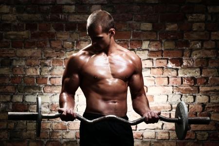 jeune mec: Jeune homme avec un corps muscl� avec halt�res sur le mur de brique