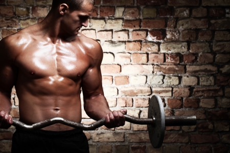 weight lifting: Young guy with muscular body with barbell over brick wall Stock Photo