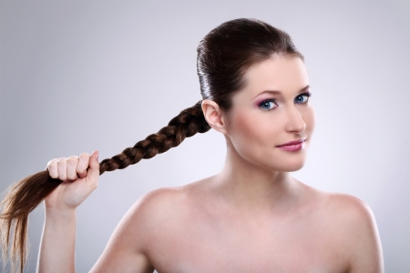tress: Beautiful woman holding her hair tress over gray background Stock Photo