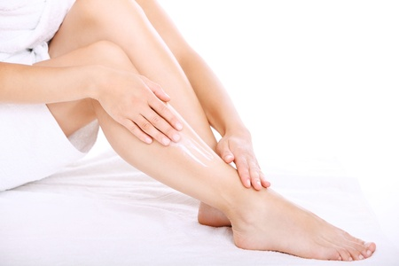 Woman applying moisturizer cream on the legs over white background  Stock Photo