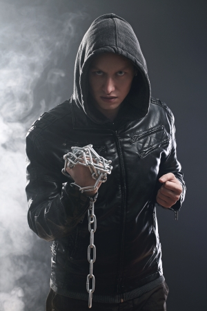 Studio portrait of street fighter with chains over his fist photo