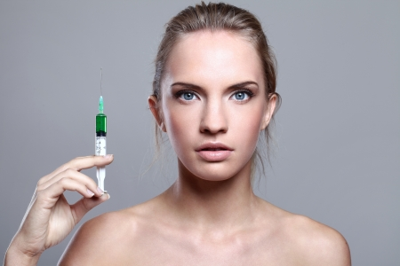 Beautiful woman and syringe with green liquid over gray background photo