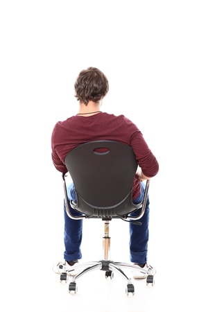 back to camera: Man sitting in a chair with his back to camera over white background