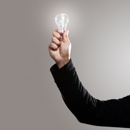 Man hand with shining lightbulb over gray background photo