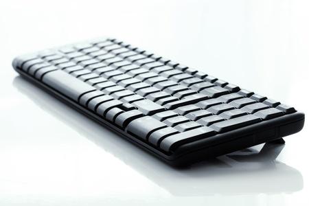 keyboard: Black wireless keyboard on white background