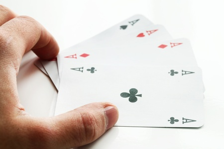 Human hand and four aces cards over white background photo