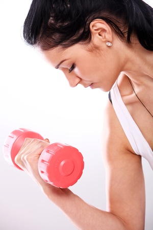 Close-up of attractive girl lifting red dumbbells photo